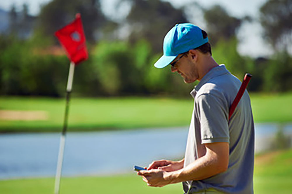 Golfer looking at his phone for some swing tips.